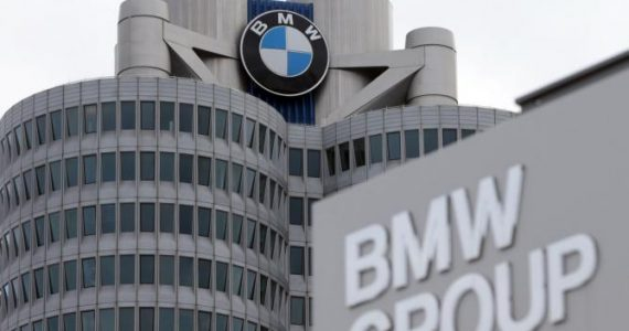 FILE - In this March 19, 2013 file photo the company sign of car manufacturer BMW is pictured in front of the headquarters in Munich, Germany. German luxury automaker BMW AG saw net profit slip 1 percent in the second quarter amid higher launch costs for new vehicles as key models approach the end of their life cycle, the company said Tuesday, Aug. 4, 2015. (AP Photo/Matthias Schrader, File)